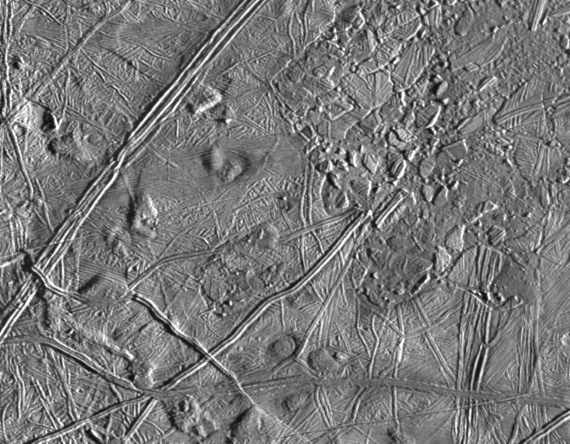 """A espaçonave Galileo viu rachaduras e fissuras na região """"caótica"""" de Europa, a evidência de um oceano líquido sob a superfície. Créditos da imagem: NASA / JPL / Galileo."""