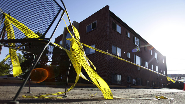 AURORA, CO - JULY 24: Yellow crime scene tape surrounds the apartment building where suspect James Holmes lived July 24, 2012 in Aurora, Colorado. Holmes, 24, is accused of killing 12 people and injuring 58 in a shooting spree on July 20 during a screening of 'The Dark Knight Rises.' According to police Holmes' apartment had more than 30 homemade grenades and 10 gallons of gas inside that was booby-trapped to go off. (Photo by Joshua Lott/Getty Images)