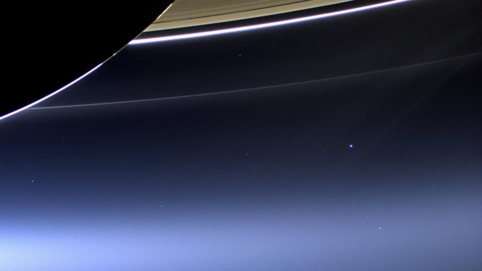 Uma lição de humildade: esse minúsculo ponto azul abaixo do majestoso Saturno é o planetinha que chamamos de casa.