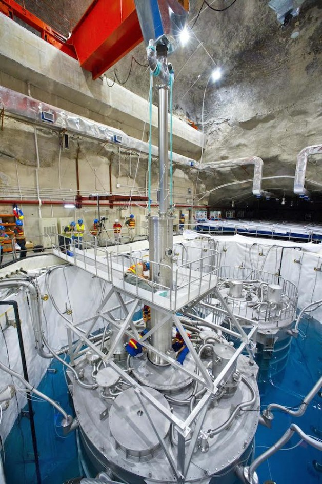 Trabalhadores instalando uma Unidade de Calibração Manual em um detector de antineutrino em Daya Bay. Esta unidade era essencial para medir com precisão as energias dos antineutrino, conforme detalhado em um novo estudo. (Crédito da foto: Roy Kaltschmidt)